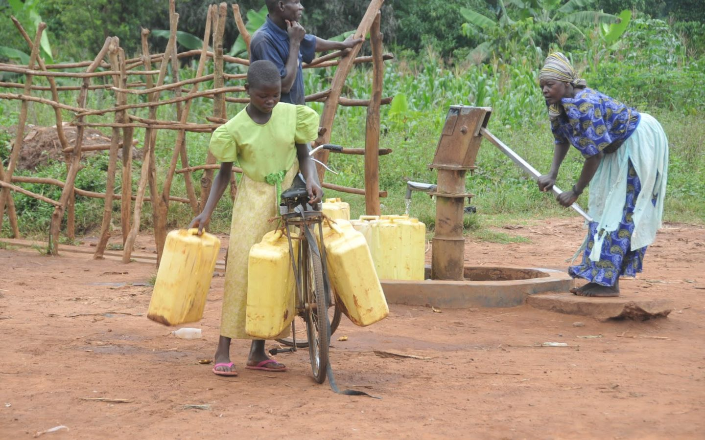 Girl collects dirty water at hand pump.