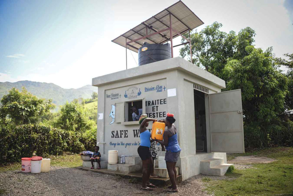 Women collect safe water from a solar-powered water project in Haiti.