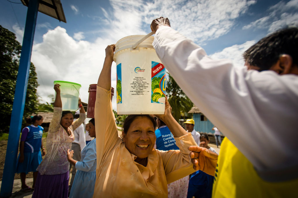A woman in Peru smiles from receiving safe water.