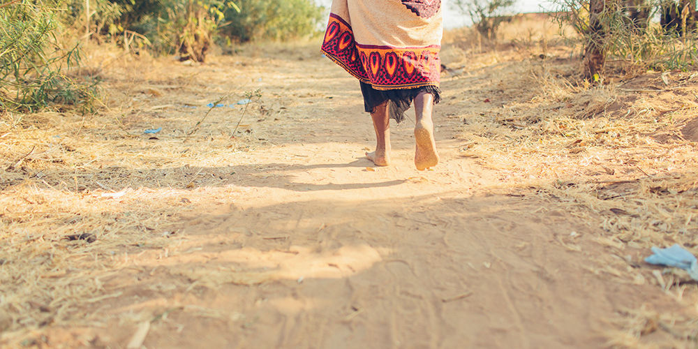 A woman in Malawi walks for water.