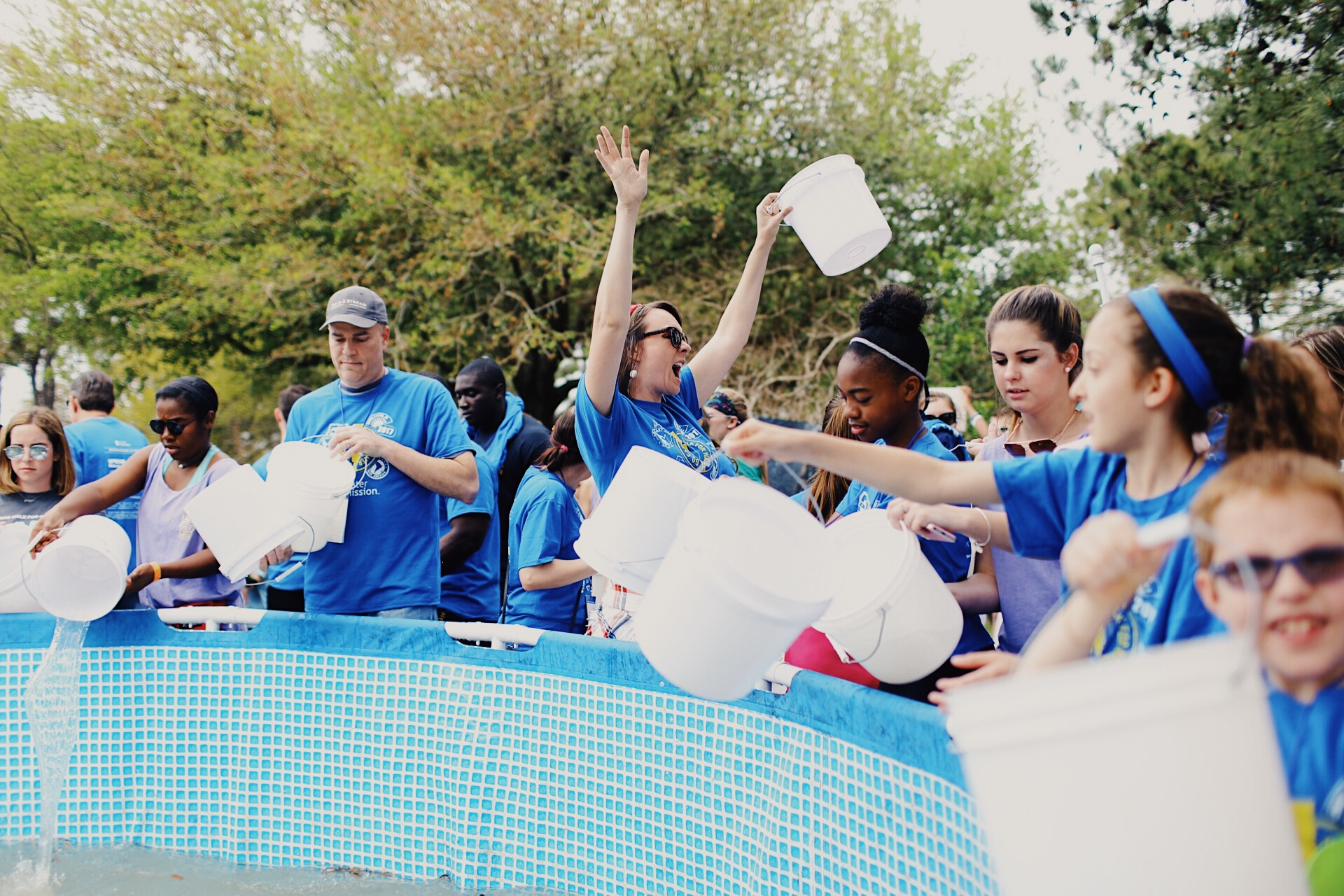 A walker celebrates at the end of Water Mission's Walk for Water as she dumps her bucket into the pool.