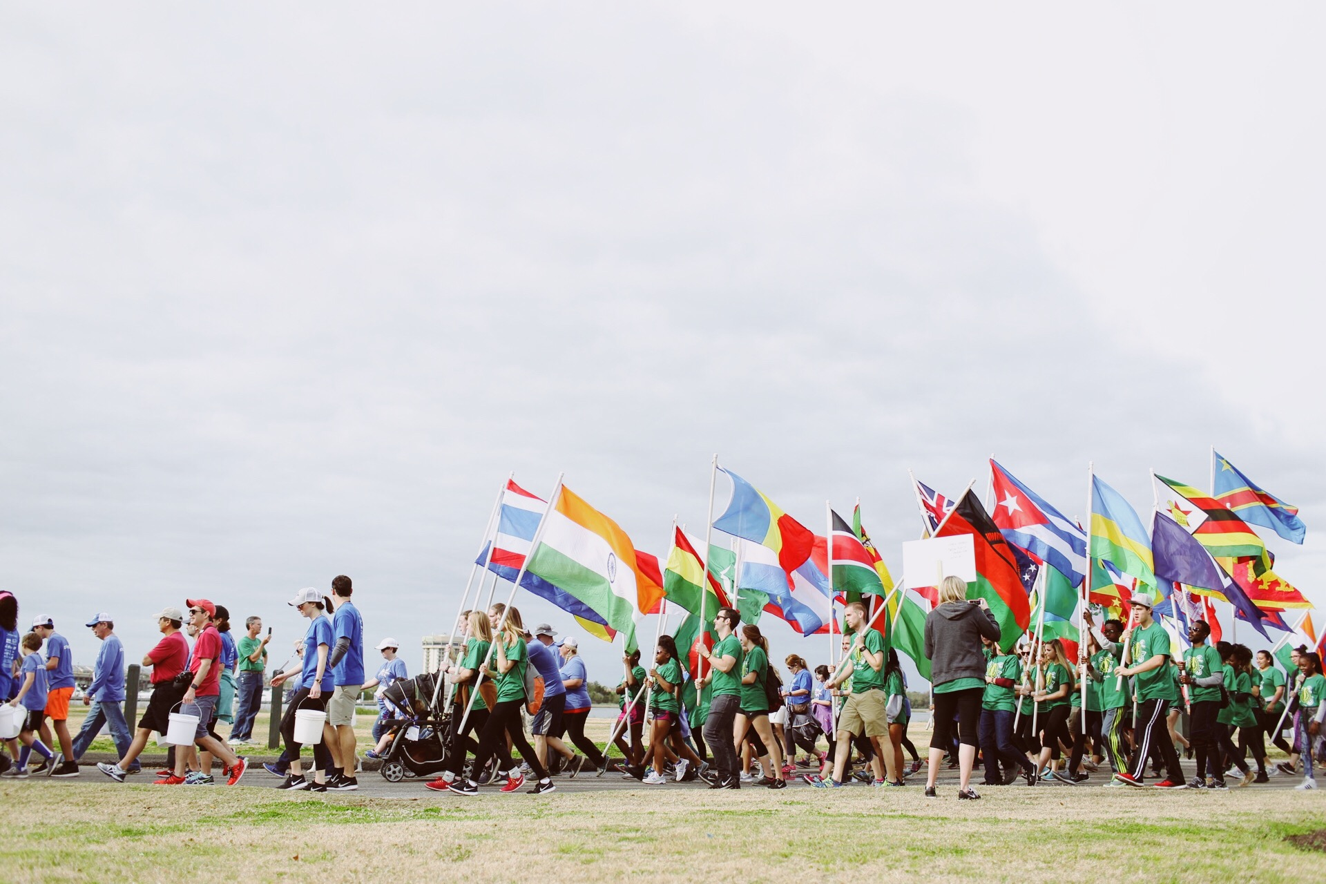 Volunteers carry flags to lead the group of 5,000 walk for water heroes.