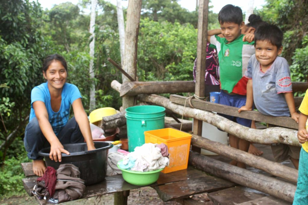 A family in Peru washes their clothes in dirty water.