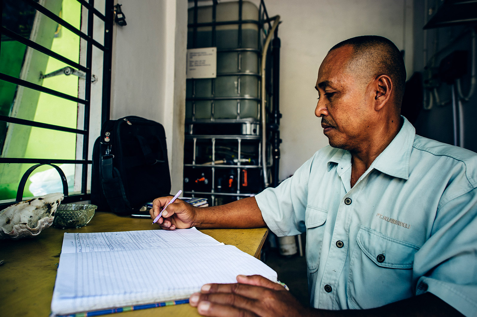 An operator calculates expenses for the safe water treatment system.