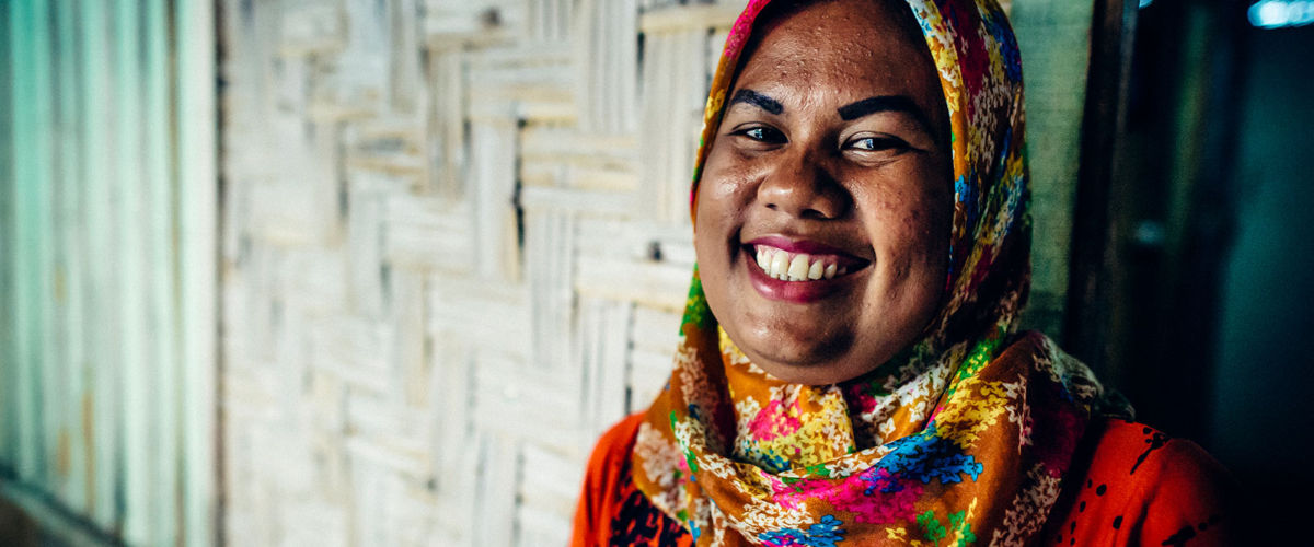 A mother in Indonesia smiles after receiving safe water.