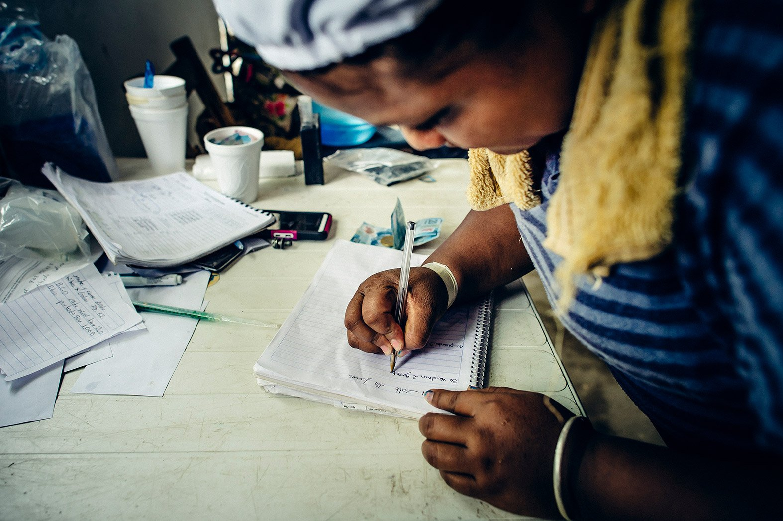 A woman records payments made for safe water.
