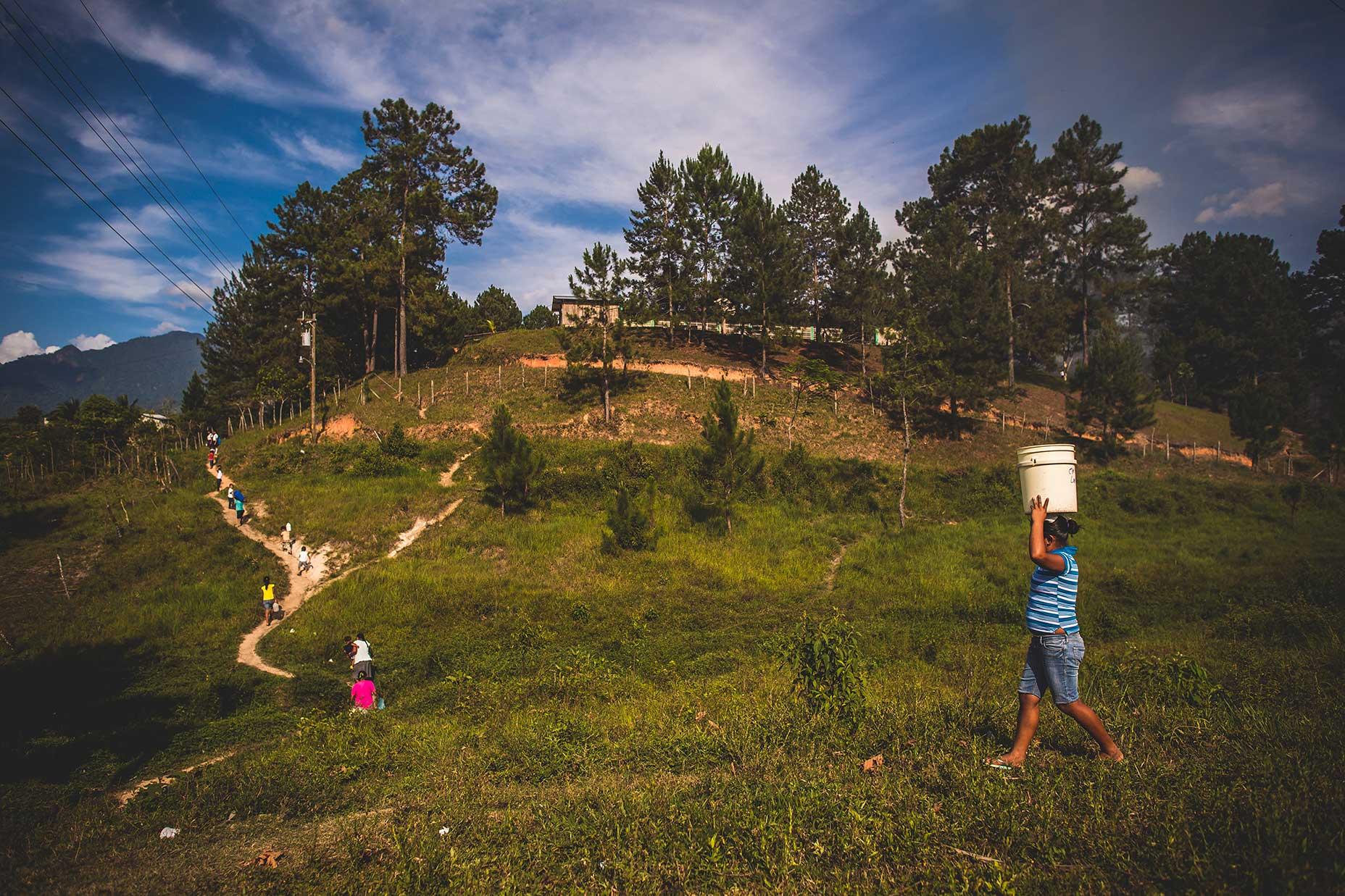 Women walk in Honduras to collect water.