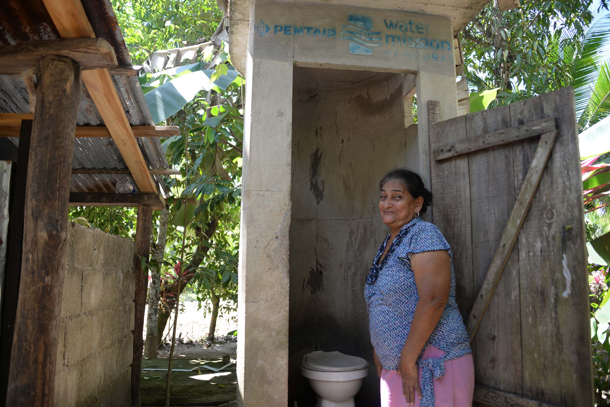 A woman in Honduras enjoys her latrine installed by Water Mission and Pentair.