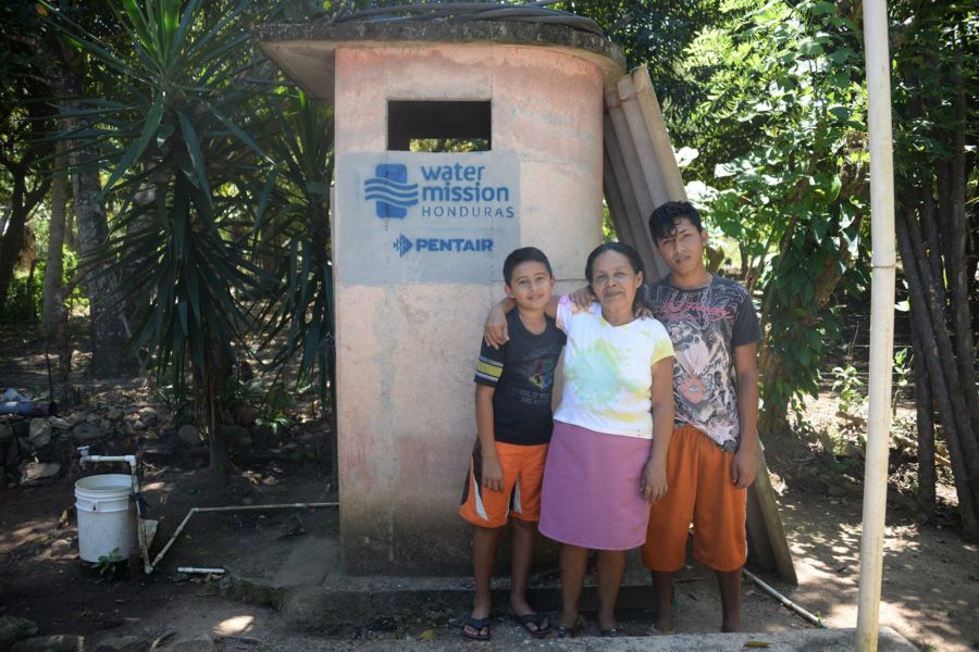 A family in Honduras enjoys their latrine installed by Water Mission and Pentair.