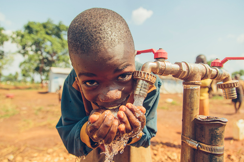 A young boy drinks safe water produced by the largest solar powered safe water treatment system.