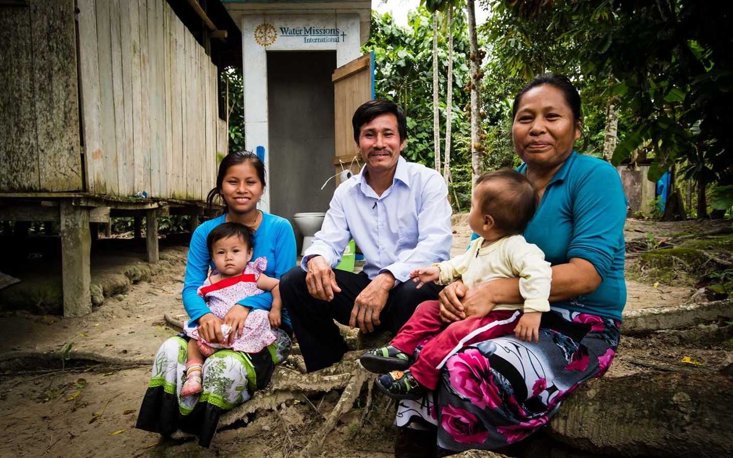 Segundo and his family sit by their latrine.