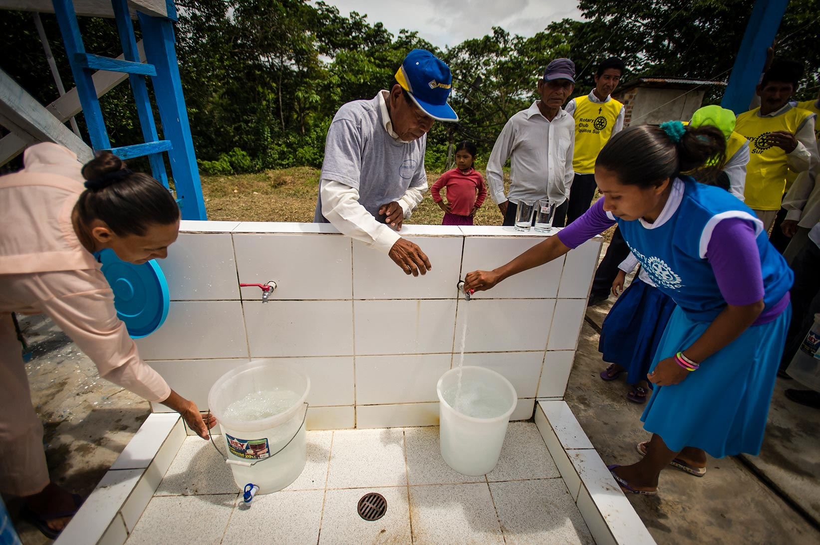 People collect safe water from the Water Mission safe water treatment system.
