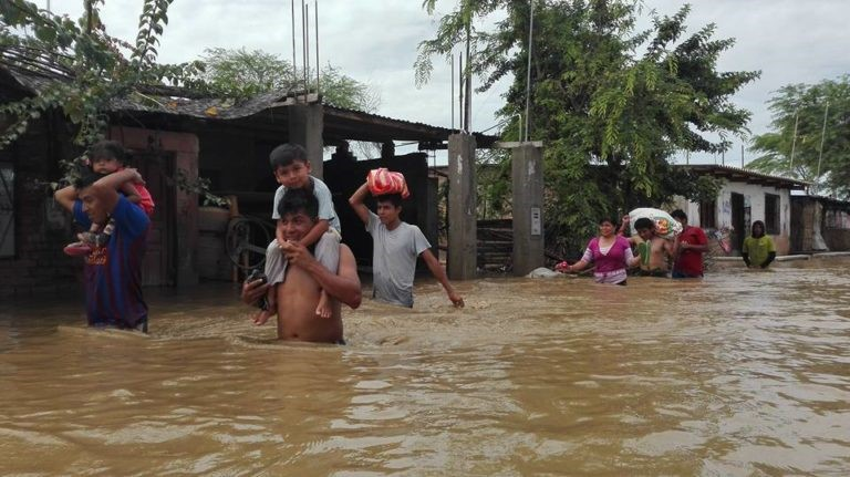 People carry their belongings on their heads after intense flooding in Peru.
