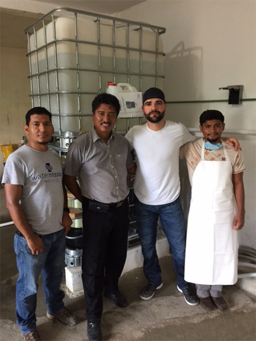 Jaime stands with Water Mission Mexico staff members at a safe water treatment system.