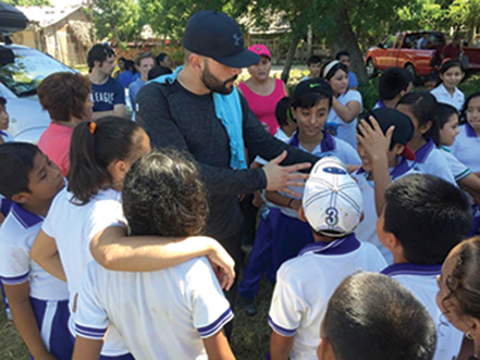 Jaime entertains local children while visiting the safe water system.