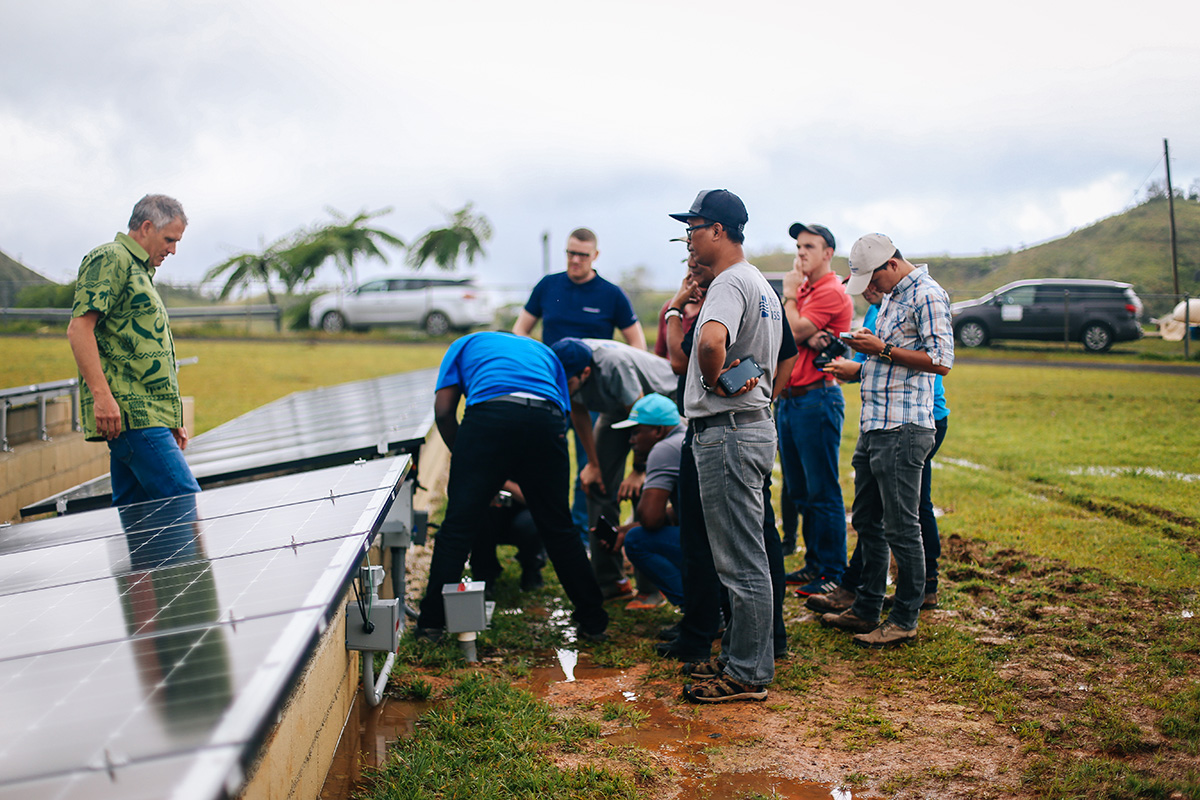 Water Mission, Grundfos, and Blue Planet Energy staff with a solar array.